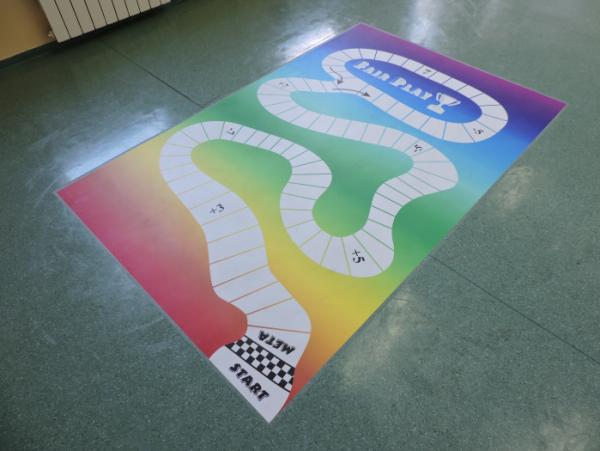 Naklejka podłogowa w szkole podstawowej, gra w kapsle.